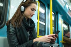 woman-listening-to-music-on-subway-train